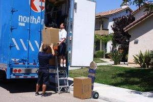 Two movers unload a moving truck